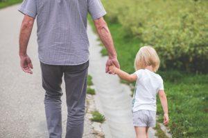 Mann nimmt Kind an die Hand, hilft