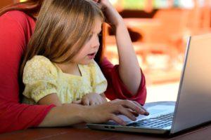 Kind sitzt an Computer und lernt