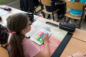 Mädchen lernt mit HIlfe von Tablet in der Schule